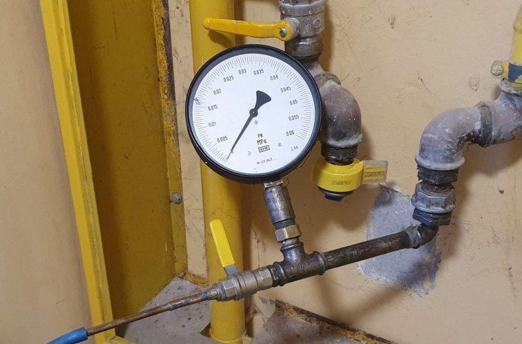 Manometr podpięty za pomocą bosta pod wewnętrzną instalację gazową w celu przeprowadzenia ciśnieniowej próby szczelności instalacji gazowej w mieszkaniu